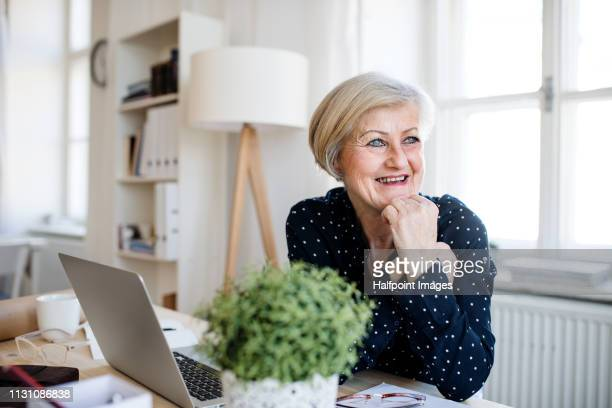 A portrait of happy active senior woman with laptop working in home office, smiling.