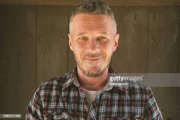 portrait of happy adult man  in front of the wooden door of his old village house - 40 44 years stock pictures, royalty-free photos & images