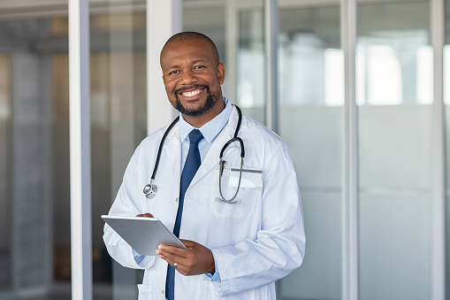 Portrait of happy african doctor at private clinic 1189303662