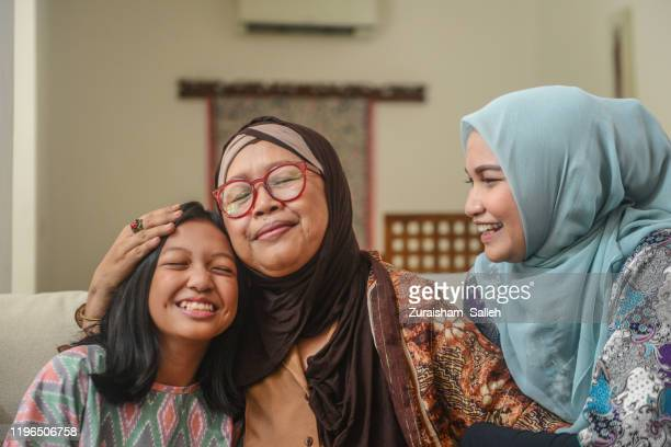 a portrait of happy asian muslim young girl with mother and grandmother sitting at home during hari raya celebration - indonesian culture stock pictures, royalty-free photos & images