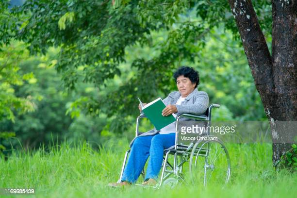portrait of happy asian old woman sitting on wheelchairs reading a book. - 1985 stock pictures, royalty-free photos & images