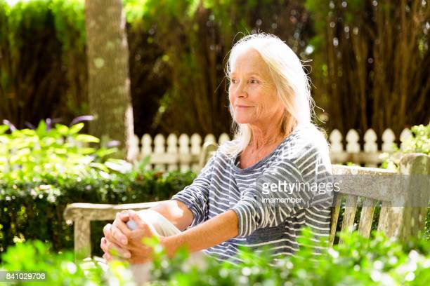 Portrait of happy, attractive mature woman sitting in the park