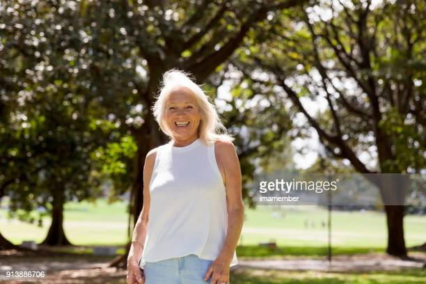 Portrait of happy, attractive mature woman standing in the park