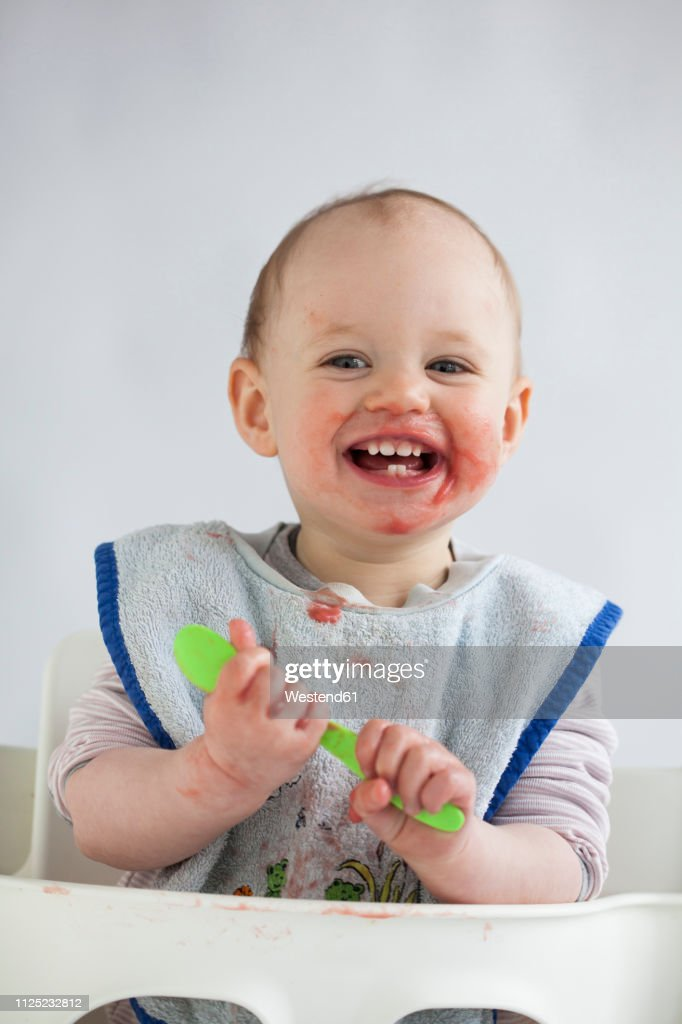 Portrait of happy baby girl with smeared face on high chair : Stock Photo