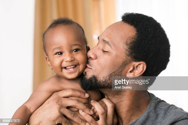 Portrait of happy baby with new teeth being kissed by his father