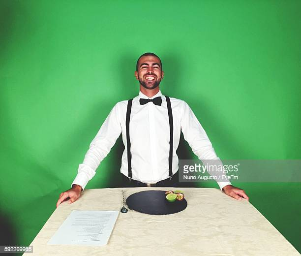 Portrait Of Happy Bartender By Table Against Green Wall