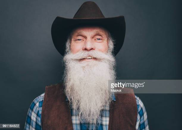 portrait of happy bearded senior man wearing cowboy hat on gray background - cowboy hat stock pictures, royalty-free photos & images