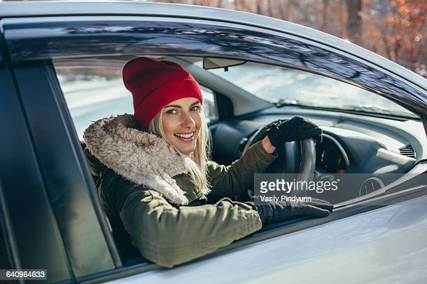 Portrait of happy beautiful woman driving car during winter