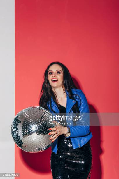 Portrait of happy beautiful woman holding disco ball against coral background