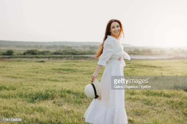 portrait of happy beautiful woman in white dress standing on grassy landscape against clear sky - 白のドレス ストックフォトと画像