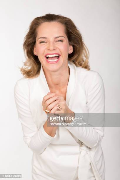 portrait of happy beautiful woman standing against white background - lady barbara stock-fotos und bilder