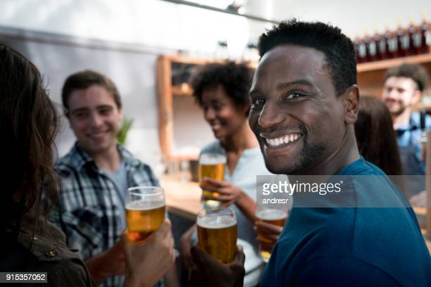 Porträt von glücklichen schwarzen Mann trinken Bier mit Freunden, Blick auf die Kamera zu Lächeln