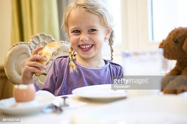 Portrait of happy blond girl at breakfast table