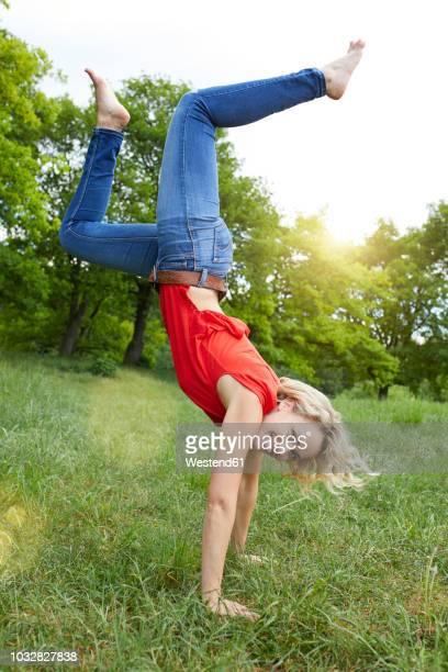 portrait of happy blond woman doing handstand on a meadow - einzelne frau über 30 stock-fotos und bilder