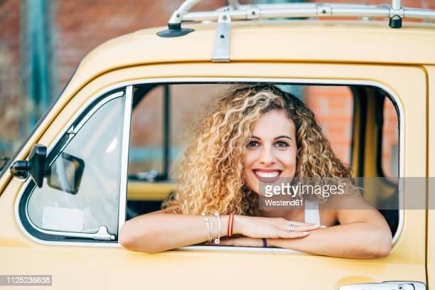 portrait of happy blond woman looking out of window of classic car - compact car stock photos and pictures