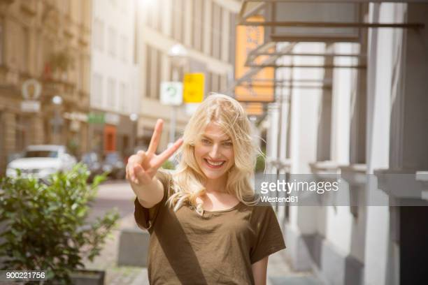 Portrait of happy blond woman showing victory sign