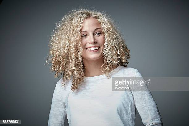 portrait of happy blond woman with curly hair - gelockt stock-fotos und bilder