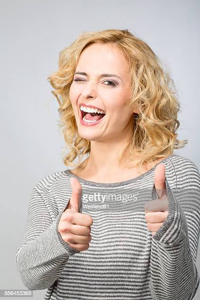 Portrait of happy blond woman with thumbs up