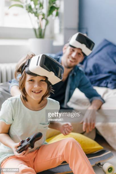 portrait of happy boy and father wearing vr glasses playing video game at home - spielsteuerung stock-fotos und bilder