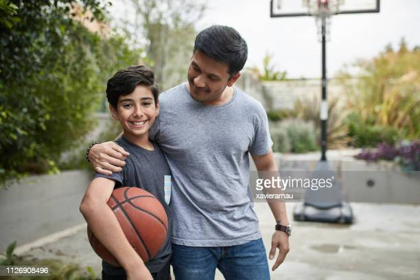 portrait of happy boy and father with basketball - pre adolescent child stock pictures, royalty-free photos & images