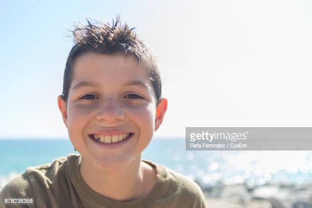 Portrait Of Happy Boy At Beach Against Clear Sky