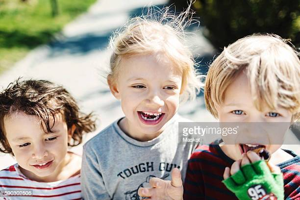 portrait of happy boy eating ice cream while walking with friends at yard - close to stock pictures, royalty-free photos & images