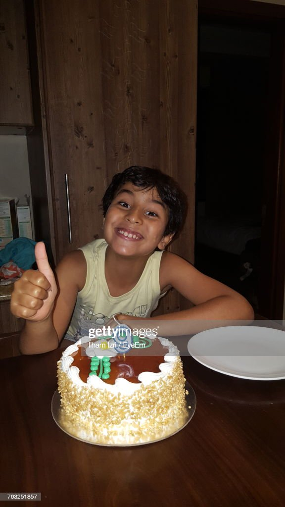 Portrait Of Happy Boy Gesturing Thumbs Up With Birthday Cake On