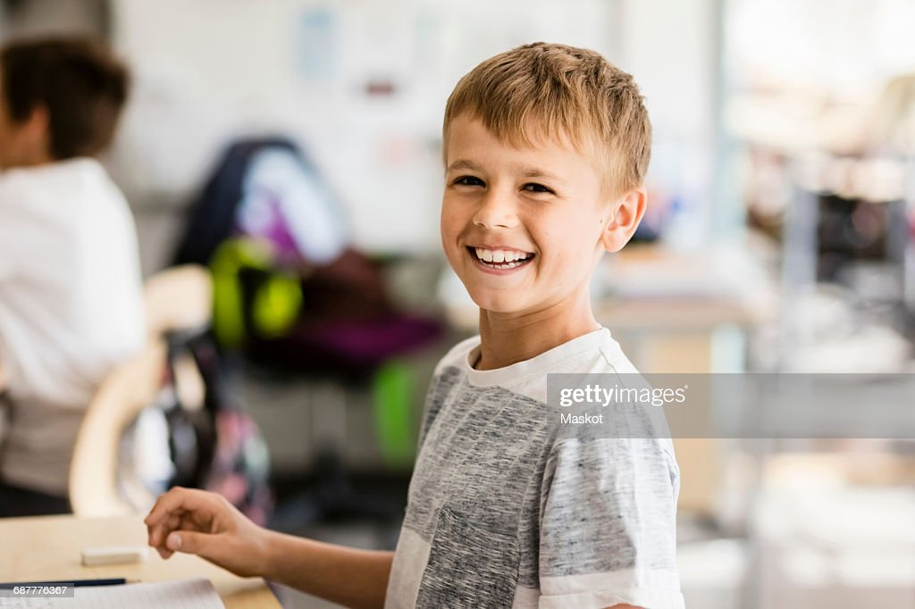 Portrait of happy boy in classroom at school : Stock Photo