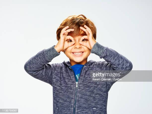 portrait of happy boy making artificial eyeglasses with hands against white background - alleen jongens stockfoto's en -beelden