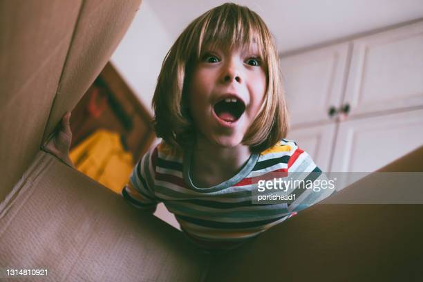 portrait of happy boy opening delivery box at home - unboxing stock pictures, royalty-free photos & images