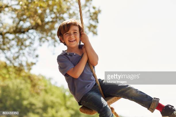 portrait of happy boy playing on swing against sky - swinging stock pictures, royalty-free photos & images