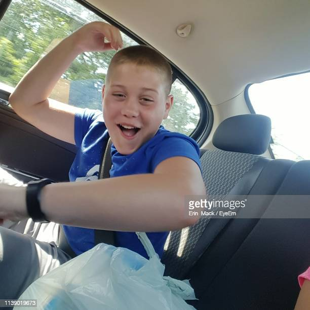 portrait of happy boy sitting in car - mack stock pictures, royalty-free photos & images