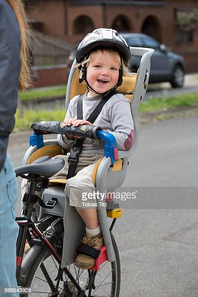 Portrait of happy boy sitting on bicycle back seat