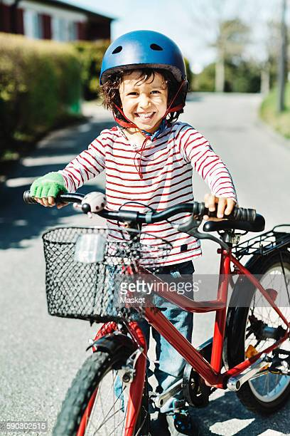 Portrait of happy boy standing with bicycle on footpath at yard