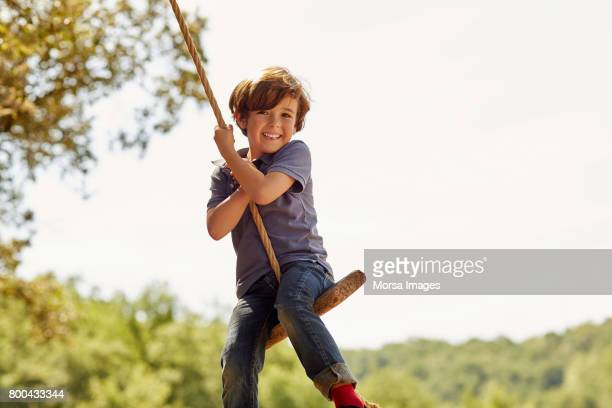 Portrait of happy boy swinging against clear sky