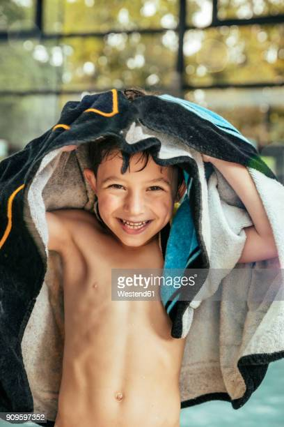 portrait of happy boy toweling himself at the poolside of an indoor swimming pool - only boys stock pictures, royalty-free photos & images