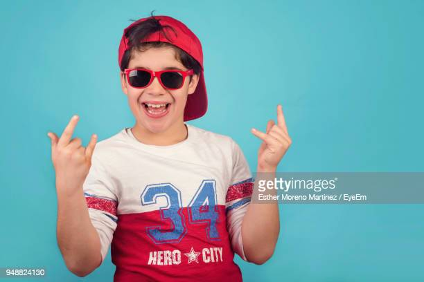 Portrait Of Happy Boy Wearing Sunglasses Standing Against Blue Background