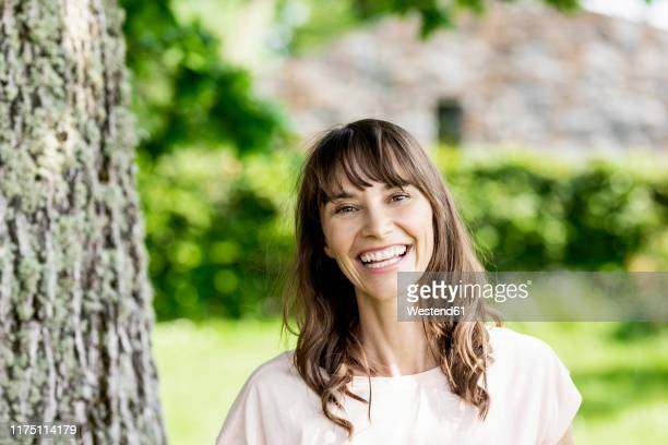 portrait of happy brunette woman at a tree trunk - einzelne frau über 40 stock-fotos und bilder