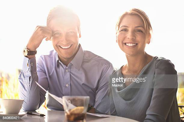 Portrait of happy business people at outdoor cafe against sky