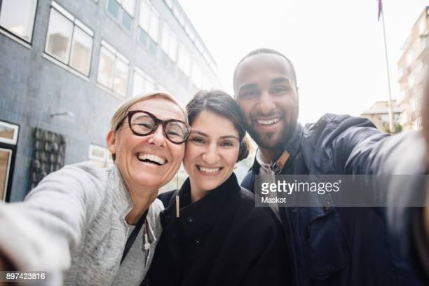 portrait of happy business people taking selfie - drei personen stock-fotos und bilder