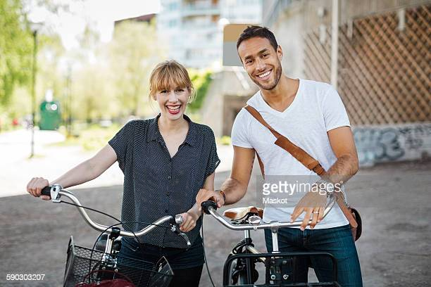 Portrait of happy business people with bicycles standing on city street
