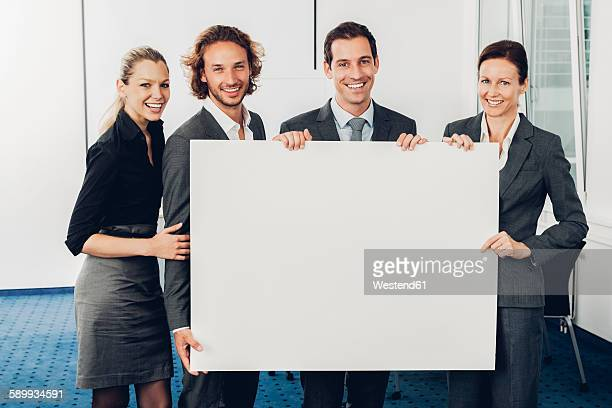Portrait of happy business team holding a blank billboard while at office