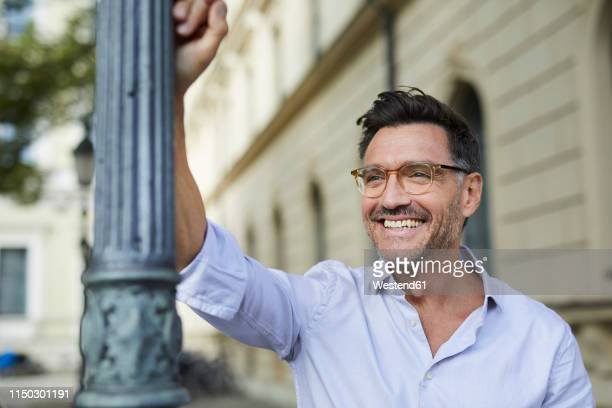 portrait of happy businessman leaning against lamp post in the city - 45 49 years stock pictures, royalty-free photos & images