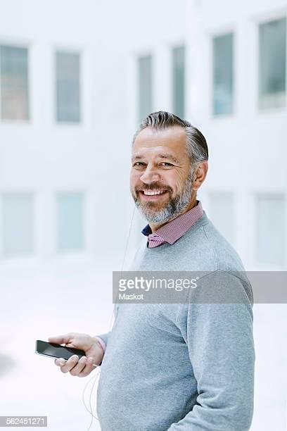 Portrait of happy businessman listening music through smart phone in office
