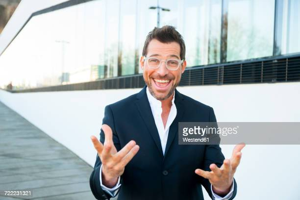 Portrait of happy businessman outdoors gesturing