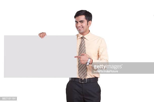 Portrait of happy businessman showing empty billboard over white background