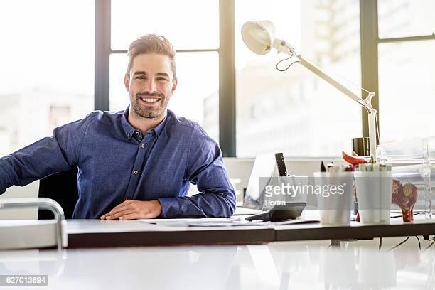 Portrait of happy businessman sitting at desk