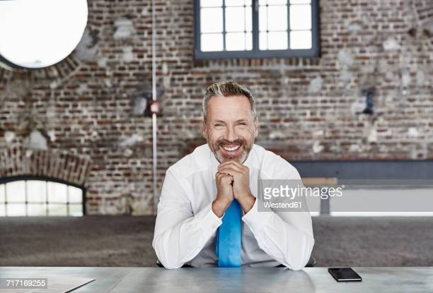 Portrait of happy businessman sitting at table in a loft