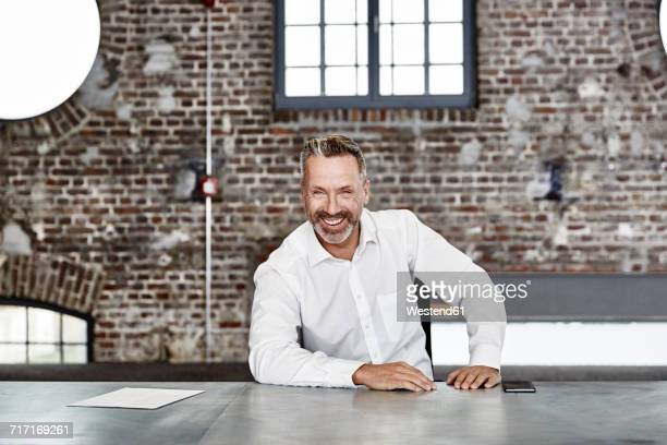 portrait of happy businessman sitting at table in a loft - weißes hemd stock-fotos und bilder
