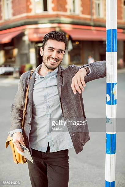 Portrait of happy businessman standing on city street